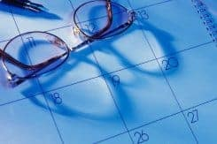 Desk calendar with pen and reading glasses